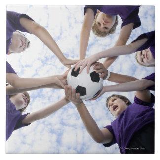 Boys holding soccer ball in huddle large square tile