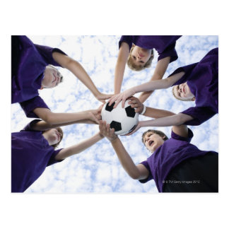 Boys holding soccer ball in huddle postcard