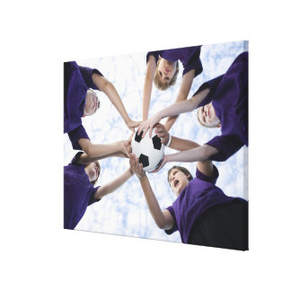 Boys holding soccer ball in huddle stretched canvas print