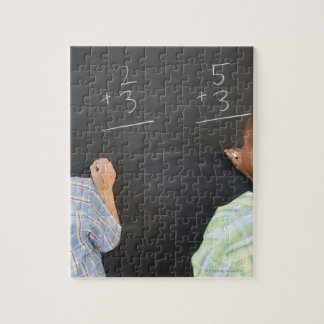 Boys solving math problems on blackboard jigsaw puzzle