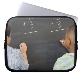 Boys solving math problems on blackboard laptop sleeve