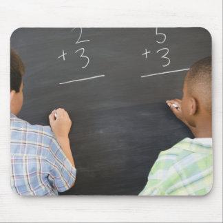 Boys solving math problems on blackboard mousepads