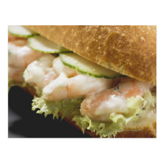 Bread roll filled with shrimps, cucumber and postcard