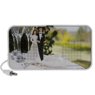 Bride and groom figurine on table by champagne notebook speaker