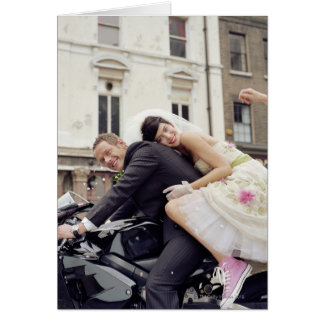 Bride and groom on motorbike, smiling, portrait greeting card