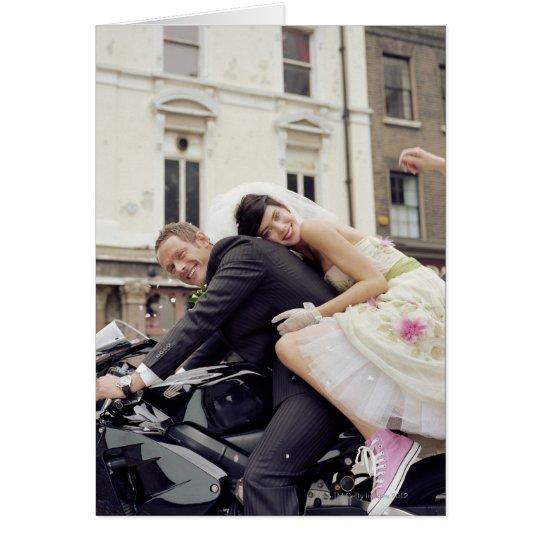 Bride and groom on motorbike, smiling, portrait card