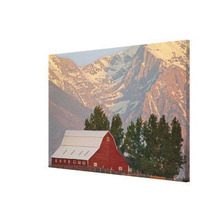 Bright red barn against Mission Mountains in Canvas Prints