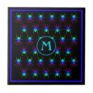 Bright spiders monogram on black tile