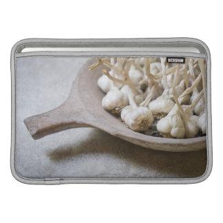 Bulbs of garlic in an earthenware bowl sleeve for MacBook air