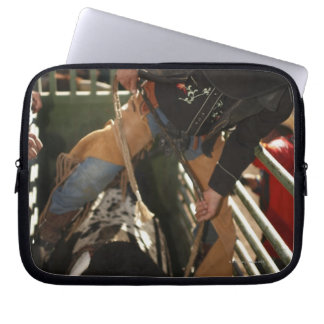 Bull rider tying rope on bull in the chute laptop sleeve