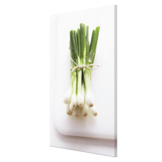 Bunch of spring onions on white chopping board canvas print