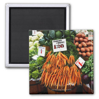 Bunches of carrots and vegetables on market magnet