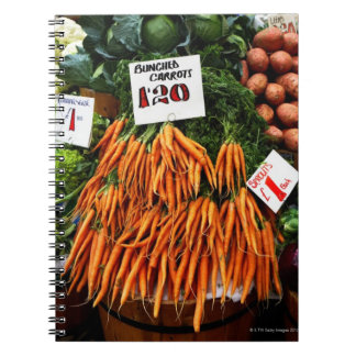 Bunches of carrots and vegetables on market notebook