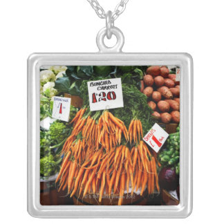 Bunches of carrots and vegetables on market silver plated necklace