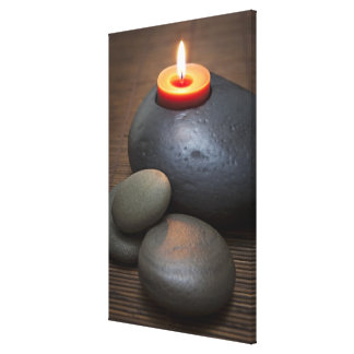 Burning candle flame with rocks in tranquil canvas print