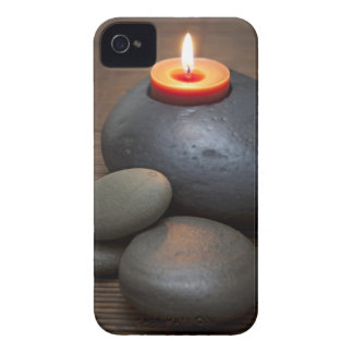 Burning candle flame with rocks in tranquil iPhone 4 cases