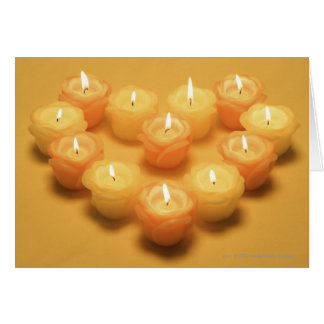 Burning candles arranged in a heart shape card