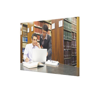 Business people doing research in library canvas print
