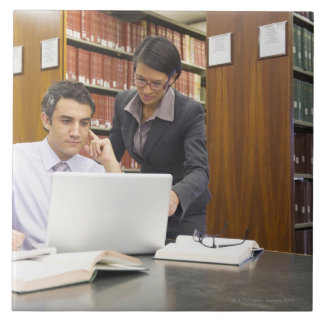 Business people doing research in library large square tile