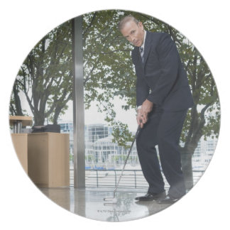 Businessman playing golf in an office plate