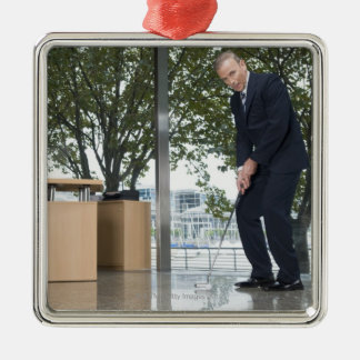 Businessman playing golf in an office Silver-Colored square decoration