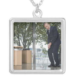 Businessman playing golf in an office silver plated necklace