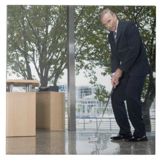 Businessman playing golf in an office tile