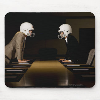 Businesswomen in face-off wearing football mouse mat