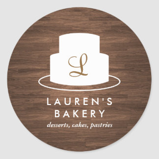 Cake Monogram Logo in White on Brown Woodgrain Round Sticker