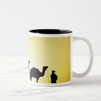 Camels and camel driver silhouetted at sunset, 2 Two-Tone coffee mug