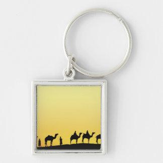 Camels and camel driver silhouetted at sunset, 3 key ring
