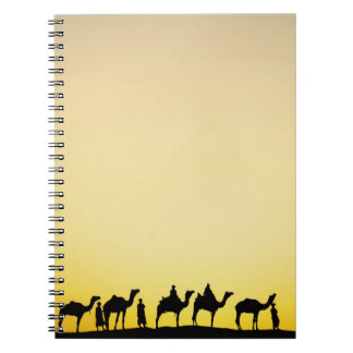 Camels and camel driver silhouetted at sunset, 4 notebooks