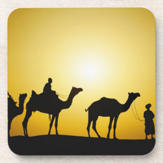 Camels and camel driver silhouetted at sunset, coaster