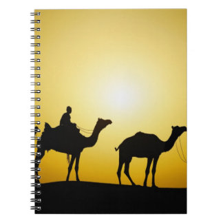 Camels and camel driver silhouetted at sunset, notebook