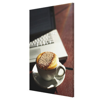 Cappuccino in front of laptop canvas print