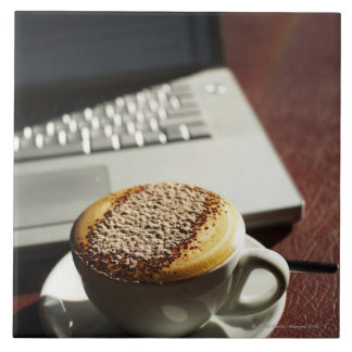 Cappuccino in front of laptop tile
