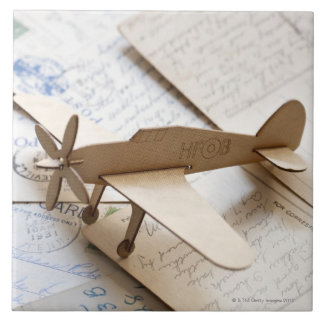 Carboard airplane on postcards tile