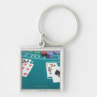 Cards and chips on betting table Silver-Colored square key ring