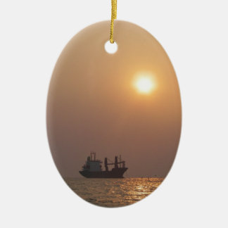 Cargo Ship Under A Hazy Sun Ceramic Oval Decoration