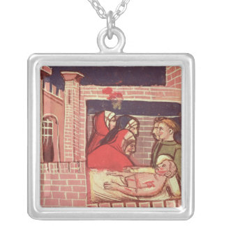 Caring for an injured man in a castle silver plated necklace