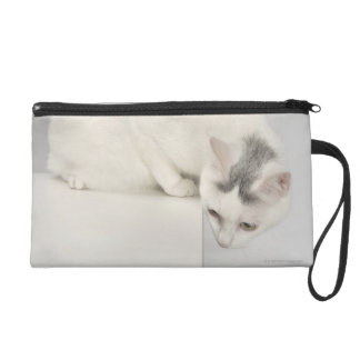 Cat looking over an edge wristlet purse