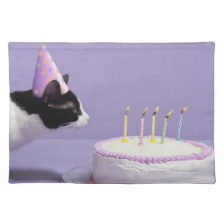 Cat wearing birthday hat blowing out candles placemat