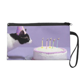 Cat wearing birthday hat blowing out candles wristlet clutch