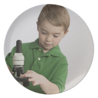 Caucasian boy using microscope plate