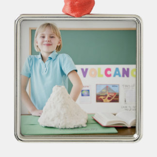 Caucasian girl standing with model volcano christmas ornament