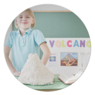Caucasian girl standing with model volcano plate