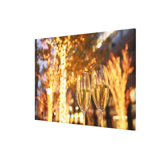 Champagne glasses toasting Christmas on city Canvas Prints