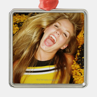 Cheerleader flipping hair, laughing, surrounded christmas ornament
