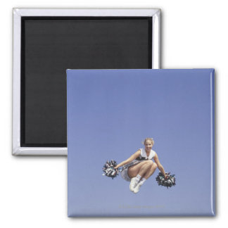 Cheerleader jumping, low angle view, portrait fridge magnets