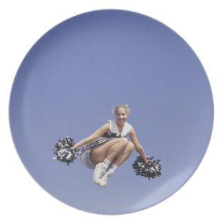 Cheerleader jumping, low angle view, portrait dinner plates
